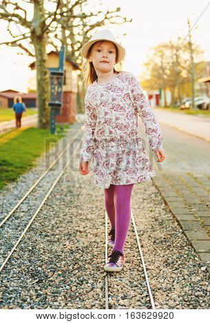 5-6 year old little girl playing outdoors at sunset, wearing hat, beautiful dress, purple tights and shoes