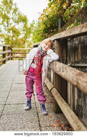 Outdoor portrait of a cute little girl wearing red trousers, colorful boots and white knitted jacket