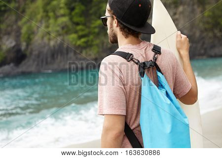 Back Shot Of Caucasian Man With Blue Bag Holding Surfboard, Watching His Friends Surfing, Riding Gia