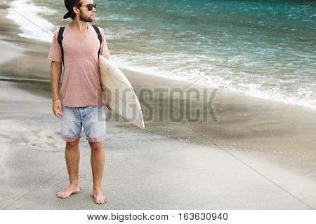 Stylish Young Barefooted Surfing Instructor Wearing Sunglasses Holding Surfboard Under His Arm, Stan
