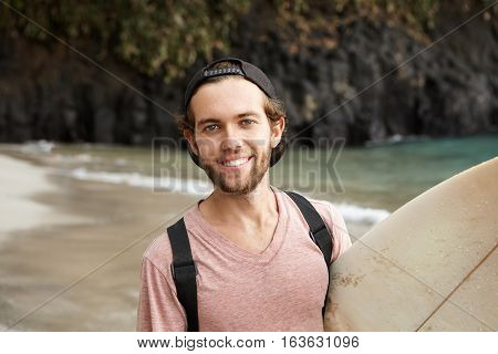 Happy Young Surfer In Snapback Looking And Smiling Cheerfully At Camera After Winning Sports Contest