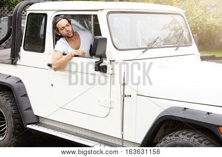 People, Lifestyle And Travel. Stylish Young Man Driving His White Four-wheel Drive Vehicle, Sticking