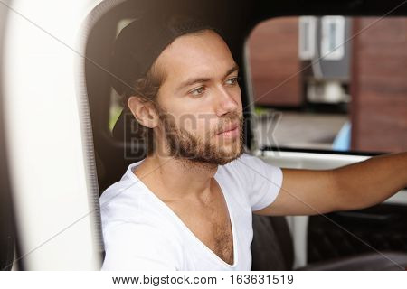 Close Up View Of Attractive Young Bearded Man In Snapback Sitting Inside Cabin Of His White Jeep, Go