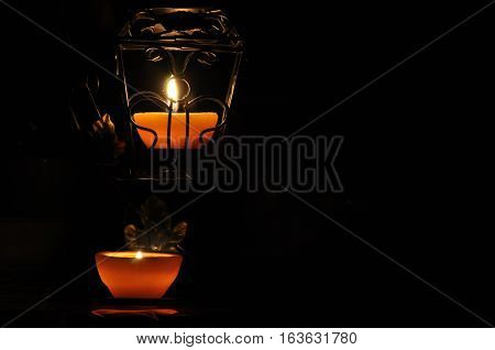 Lamp candle shining in the darkness. Challis flame. Artistic composition. Lighting.