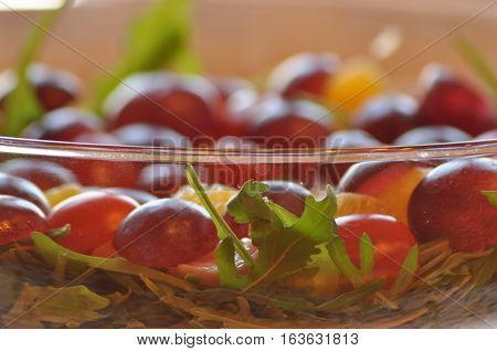 Salad in a glass dish. Rocket salad with grapes.