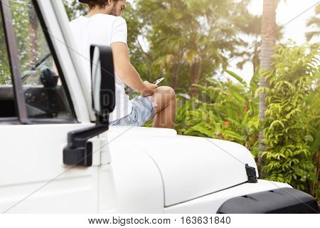 People, Technology And Leisure Concept. Young Stylish Man Using Smart Phone, Sitting On Bonnet Of Hi
