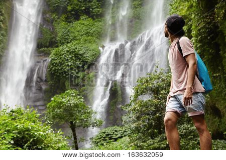 People, Wildlife And Adventure Concept. Fashionable Young Adventurer With Backpack Contemplating Wat