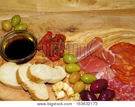 antipasto board with a selection of meats olives cheese tomatoes and bread with a wooden background