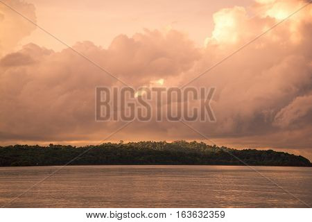 Orange sky at a sunset and island litted by sun