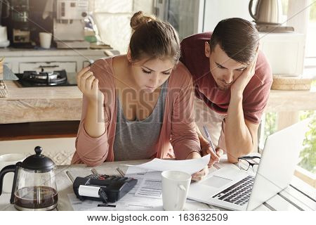 Young Married Couple With Many Debts Doing Paperwork Together, Reviewing Their Bills, Planning Famil