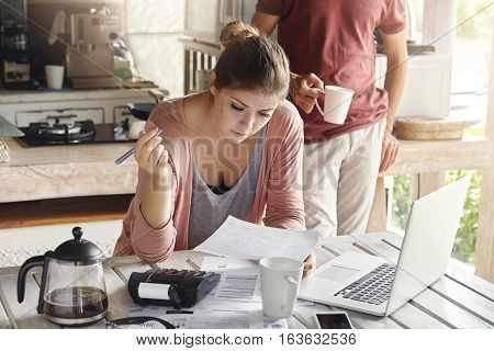 Young Caucasian Family Facing Financial Problem. Casual Woman Holding Piece Of Paper And Pen, Fillin