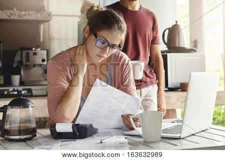 Unhappy Beautiful Woman Wearing Spectacles Having Concentrated Look Reading Notification Form Bank O