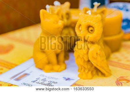 Natural handmade artisanal beeswax candles shaped like a cat and an owl at a local outdoor farmers market in Nice France