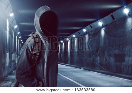 Hacker anonymous standing in the underground tunnel