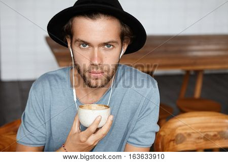 Close Up Portrait Of Handsome Blue-eyed Young Man With Stylish Beard Wearing Black Hat And Casual T-