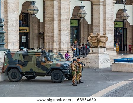 Rome. Italy - October 11, 2016: Two officers carrying Beretta assault rifles stand next to an armored vehicle humvee in Piazza della Repubblica