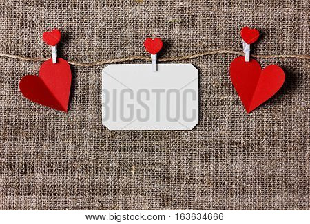 Valentines day card with hearts on a sacking, hessian or burlap background. Love message concept.