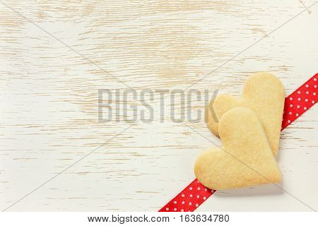 Valentines day card with Shortbread cookies in shape of heart on a wooden background.
