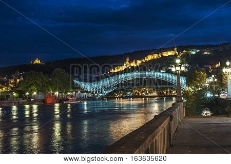Georgia, Tbilisi night . View from the embankment of the Kura at the Bridge of Peace , Narikala Fortress , Metekhi Cathedral .