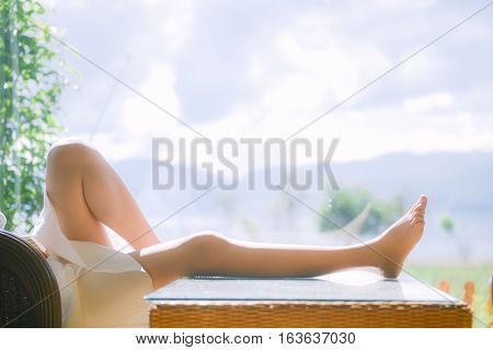 Young woman puts her legs on the table in room by the window
