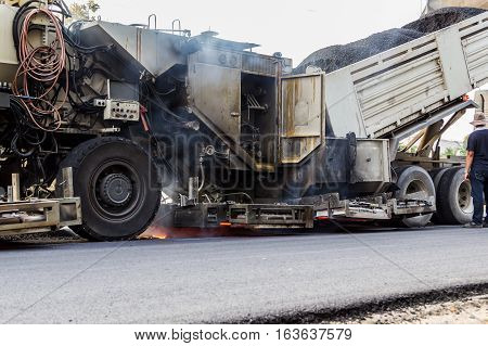 Truck Is Unloading Asphalt To Machine For Repair Road
