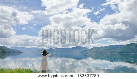 Single young Chinese woman in white long skirt stands on wasted platform on bank of Lugu lake, listening to music, back to camera, at Daluoshui village, Lijiang, China