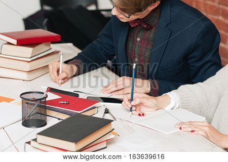 Young man studying with girl at library. Workplace of pair of students grinding away at library. Teamwork, education, learning, library, lesson concept