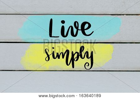 Live simply handwritten message over painted wooden background