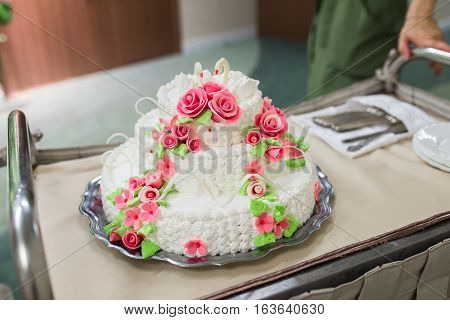 Wedding cake with red roses on table in wedding day