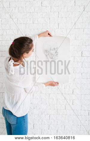 Woman looking at pencil portrait against wall. Artist evaluating her performance in workshop, new drawing style training. Art, study, creativity, criticism, craft concept