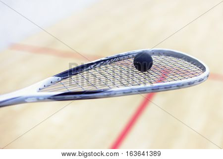 squash racket and ball. Racquetball equipment. Squash ball on squash racket with court on the background. Photo with toning and selective focus