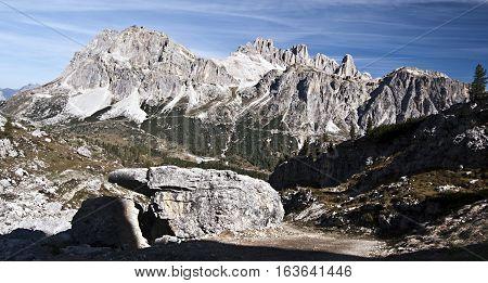 panorama of Laguazoi and Tofana mountain group in Dolomites near Cortina d'Ampezzo above Passo Falzarego with big stone on the frontyard during hiking from Passo Falzarego to Monte Nuvolau peak