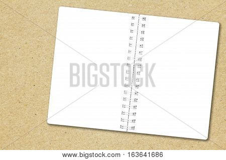Open notebook paper page on recycled brown paper background for design with copy space for text or image.