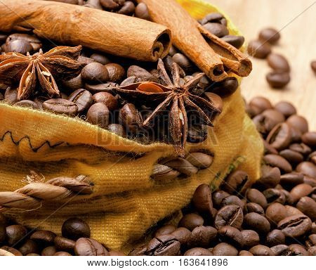 Coffee beans cinnamon and anise in a bag wood background