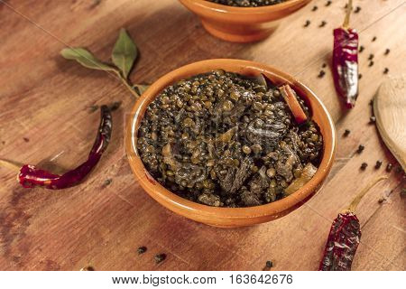 A photo of a lentil stew, shot on a dark wooden texture with bay leaves and peppers scattered around