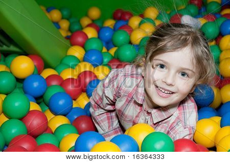 Little girl playing in colorful balls