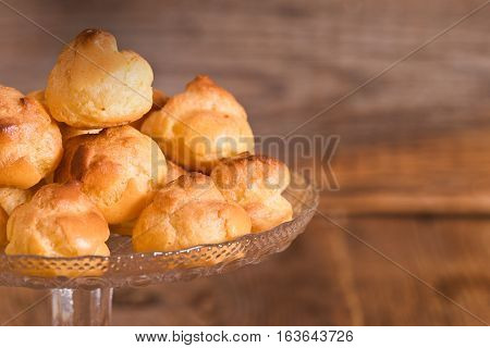 Group of sweet cream puffs on glass tray.