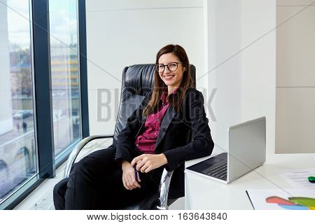 Business woman smiling behind a desk in  modern office at  window.