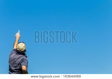 Man raised hand pointing towards summer blue sky rear unidentified photo image