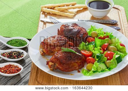 Grilled Chicken Thighs With Green Fresh Salad On White Platter