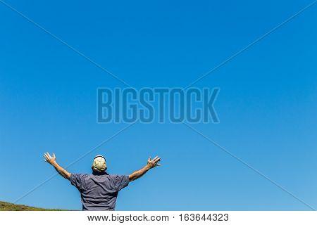 Man raised hands towards summer blue sky rear unidentified photo image