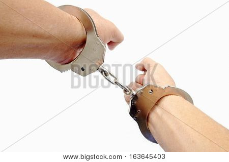 Close-up handcuffs on a hand on white background
