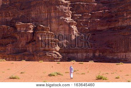Bedouin man below huge cliffs in Wadi Rum desert Jordan