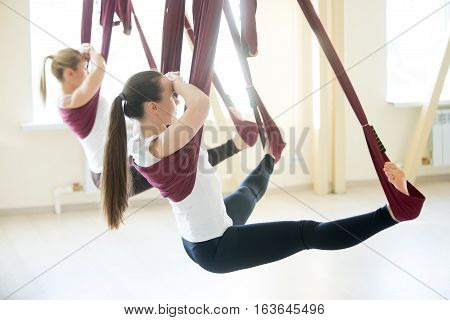 Two young pretty yogi women doing aerial yoga practice in purple hammocks in fitness club. Beautiful models working out in class. Variation of Wide Angle Seated Forward Bend, Upavishtha Konasana pose