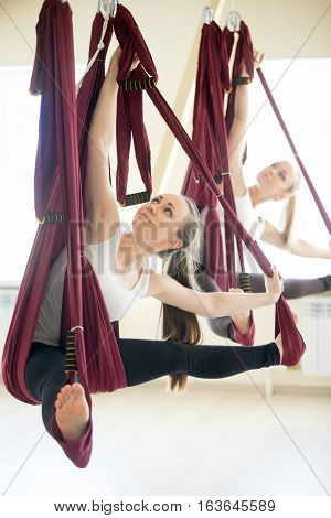 Two young attractive women doing aerial yoga practice in purple hammocks in fitness club. Beautiful models working out in class. Variation of Parivrtta Upavistha Konasana, Revolved Seated Angle Pose
