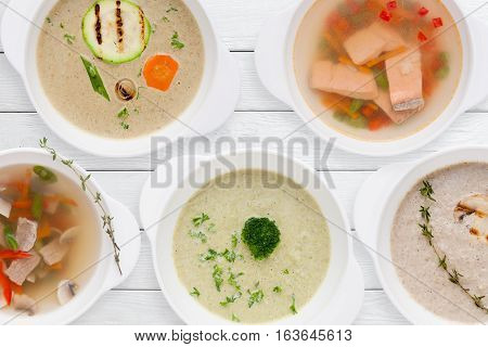 Set of tasty soups on white table flat lay. Top view on variation of restaurant hot dishes. Worldwide cuisine, healthy food, lunch, menu concept