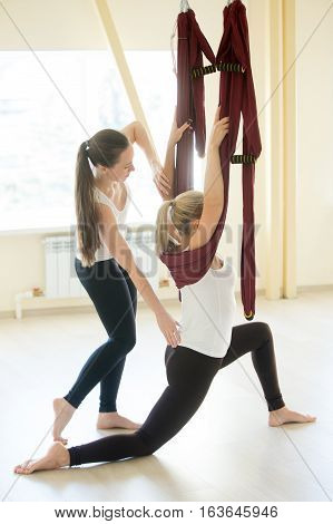 Aerial yoga lesson. Young beautiful female instructor coaching her student in antigravity yoga in fitness club. Partners women working out in purple hammocks, doing low lunge exercise. Full length