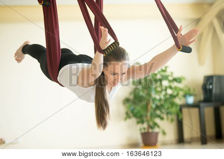 Young beautiful yogi woman doing aerial yoga practice in purple hammock in fitness club. Attractive model working out in class. Flying in hammock in variation of Locust pose, Salabhasana. Full length