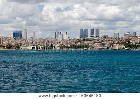ISTANBUL TURKEY - JUNE 8 2016: View across the Bosphorus towards the Besiktas district of Istanbul Turkey on a cloudy Summer day. Along the shoreline is the Bahcesehir University