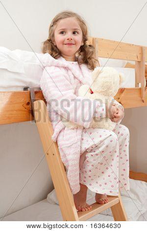 Cute girl in pyjama hugging no-name teddy bear